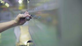 Skruvande skruvar för oigenkännlig anställd som drar åt skruvarna genom att använda skruvmejseln, skiftnyckel på en industriell f lager videofilmer