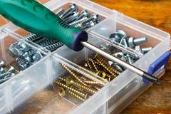 Skruvar och bultar i lagringsasken med skruvmejsel på arbetsbänken Royaltyfri Fotografi