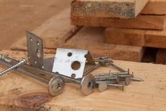 Skruvar och spikar för att bygga ett trähus Sammanfogande trästrålar Byggnationer Arkivfoto