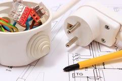 Skruvmejsel, elektrisk ask och elektrisk propp på byggnadsritning Arkivbild
