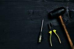 Skruvmejslar, hammare, plattång och hjälpmedel på en svart trätabell Top beskådar royaltyfria foton