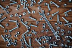 Skruvnyckel och muttrar med bultar på en träyttersida Arkivfoto