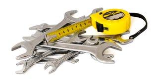 Skruvnyckel, skiftnyckel, tangent och roulett, måttband på Arkivfoto