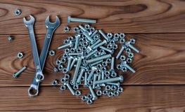 Skruvnycklar och muttrar med bultar på en träyttersida Arkivfoto