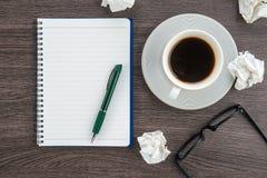 Skrynkla papper, anteckningsboken och pennan med koppen kaffe Fotografering för Bildbyråer