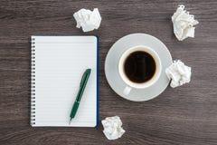 Skrynkla papper, anteckningsboken och pennan med koppen kaffe royaltyfri fotografi