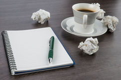 Skrynkla papper, anteckningsboken och pennan med koppen kaffe royaltyfria foton