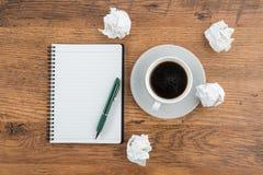 Skrynkla papper, anteckningsboken och pennan med koppen kaffe royaltyfri foto