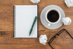 Skrynkla papper, anteckningsboken och pennan med koppen kaffe royaltyfria bilder