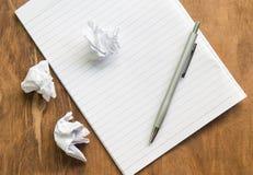 Skrynkla vitbok och skriva med anteckningsboken på träskrivbordet royaltyfria bilder