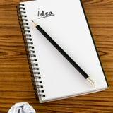 Skrynklig papper och blyertspenna med anteckningsboken Arkivbilder