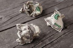 Skrynkliga dollar på en gammal trätabell royaltyfria bilder