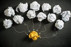 Skrynkliga pappers- symbolisera olika lösningar med ett anseende ut med en olik färg som den bästa idén arkivbild