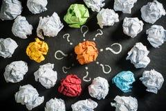Skrynkliga pappers- symbolisera olika lösningar med ett anseende ut i mitt royaltyfri fotografi