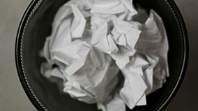 Skrynkliga pappersstycken tappade in i soptunnan arkivfilmer