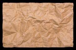 Skrynkligt kraft papper som isoleras på en svart bakgrund Arkivbilder