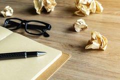 Skrynkligt papper klumpa ihop sig med den ögonexponeringsglas och anteckningsboken på det wood skrivbordet Fotografering för Bildbyråer