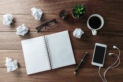 Skrynkligt papper klumpa ihop sig med koppen kaffe och anteckningsboken på träD Royaltyfria Foton