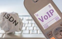 Skrynkligt papper med inskriften ISDN och den moderna telefonen med VoIP i skärmen som ett tecken av ändringen från ISDN att u royaltyfria foton