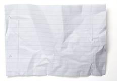 Skrynkligt papper med linjer och hål på vit Arkivbild