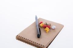 Skrynkligt papper, penna och en anteckningsbok Arkivbilder