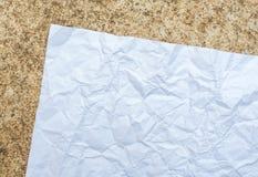 Skrynkligt papper som förläggas på cement Arkivfoto