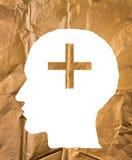 Skrynkligt papper som formas som ett mänskligt huvud och plus tecken på guld- PA Royaltyfri Fotografi