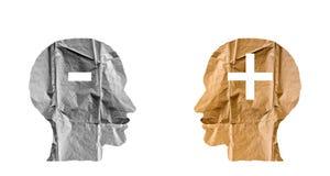 Skrynkligt papper som formas som mänskliga huvud och plus och negativ tecken arkivfoton