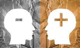 Skrynkligt papper som formas som mänskliga huvud och plus och negativ tecken Arkivbild