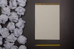 Skrynkligt pappersbollar och tomt ark av papper med blyertspennan på svart bakgrund Pappers- bunt blank kreativitet skrynkliga pa Royaltyfria Foton