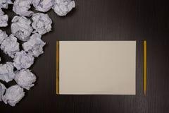 Skrynkligt pappersbollar och tomt ark av papper med blyertspennan på svart bakgrund Pappers- bunt blank kreativitet skrynkliga pa Royaltyfri Bild