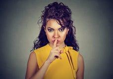 Skryta kobieta pyta z palcem na wargach shh, zaciszność zdjęcie royalty free