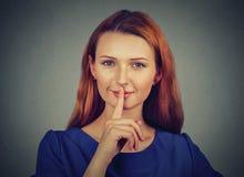 Skryta młoda kobieta umieszcza palec na wargach pyta shh, zaciszność, cisza zdjęcie stock
