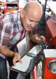 Skrzętny starszy mężczyzna robi pojazd liczbom na maszynie Zdjęcia Royalty Free