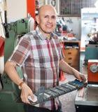 Skrzętny starszy mężczyzna robi pojazd liczbom na maszynie Obraz Stock