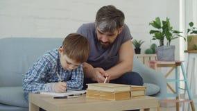 Skrzętny uczeń robi jego pracy domowej writing w ćwiczenie książce podczas gdy jego kochający ojciec pomaga on Edukacja zdjęcie wideo