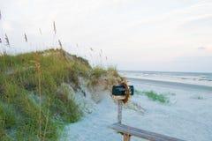 Skrzynka pocztowa w piasku przy zmierzch plażą Zdjęcia Stock