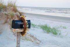 Skrzynka pocztowa w piasku przy zmierzch plażą Fotografia Stock