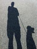 Skugga av att gå för man och för hund arkivbild