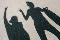 Skugga av den unga mannen och kvinnan som poserar med skateboarden royaltyfri bild