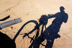Skugga av en cykel och en cyklist på asfalten, i höst fotografering för bildbyråer