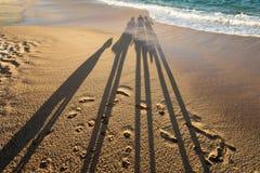 Skugga av en familj på stranden Arkivbild