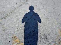 Skugga av en man i en parkeringsplats royaltyfria bilder