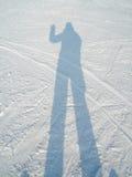 Skugga av en man i snön Arkivfoto