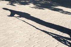Skugga av en man på sparkcykeln arkivbild