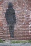 Skugga av en man på tegelstenväggen Royaltyfria Bilder
