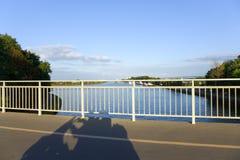 Skugga av en moped på en bro arkivbild