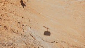Skugga av en ropewaykabinresning i den Masada öknen Bil för flyg- kabel som går upp på en solig dag Sand och vaggar Israel 4K stock video
