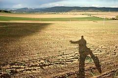 Skugga av en vinkande man i soligt höstlandskap Royaltyfri Bild