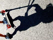 Skugga av ett barn som rider en sparkcykel Arkivfoto